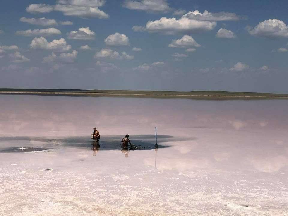 Муж и жена лопатами выкапывали грязь из озера