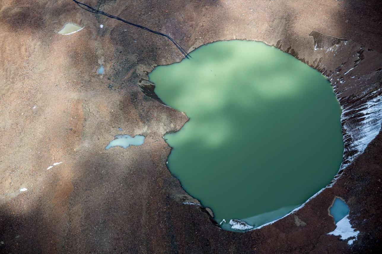 Моренное озеро с установленными на нем сифонами для откачки воды