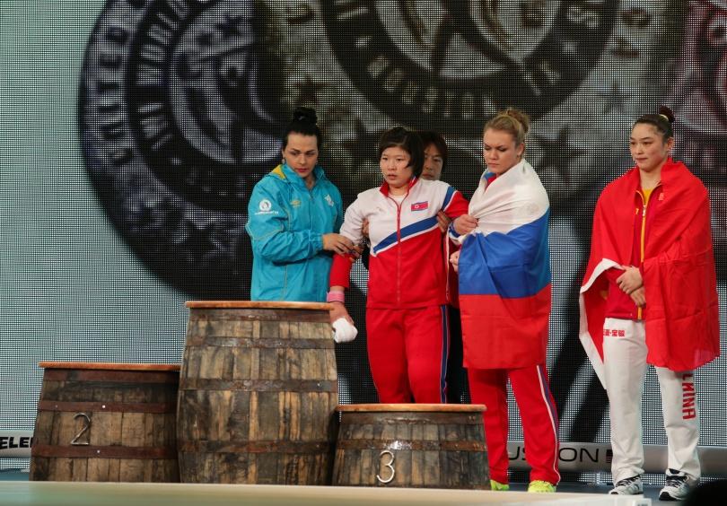 Светлана Подобедова и Ольга Зубова помогают травмированной Жон Сим Рим подняться на пьедестал почёта