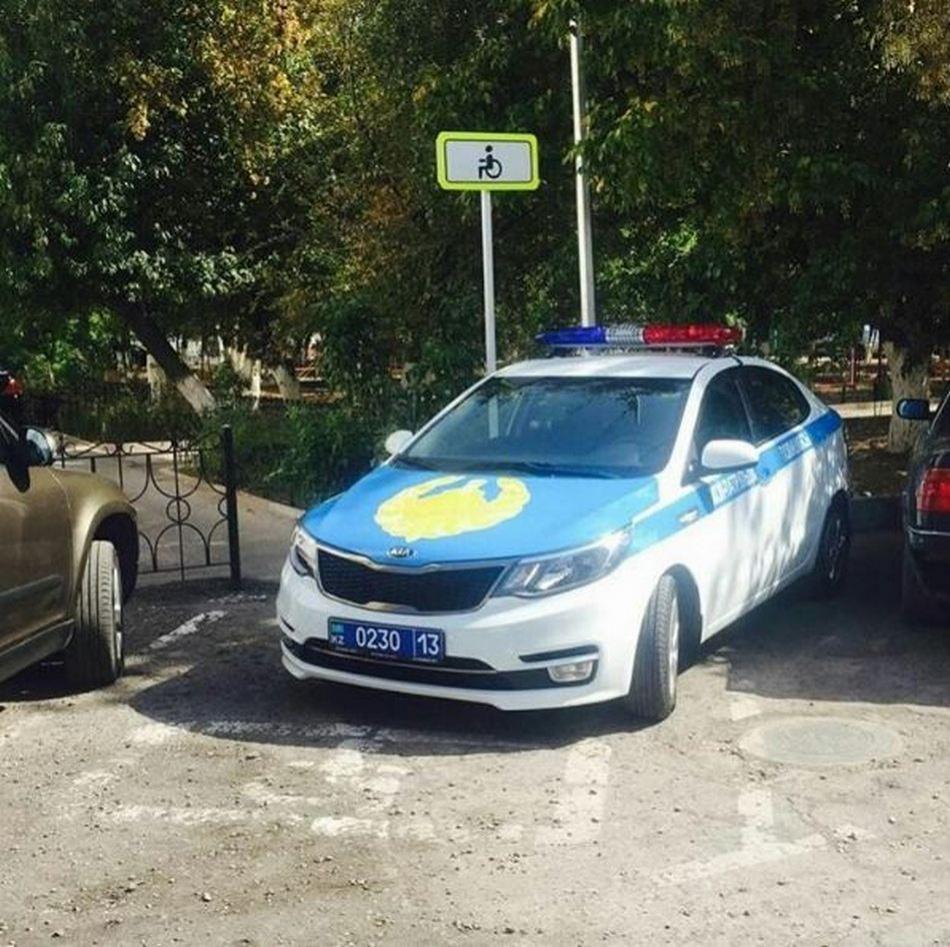 Полицейская машина на стоянке для инвалидов