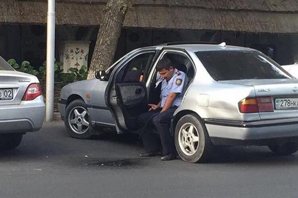 На фотографии отчётливо видно, как человек в полицейской форме мочится на асфальт