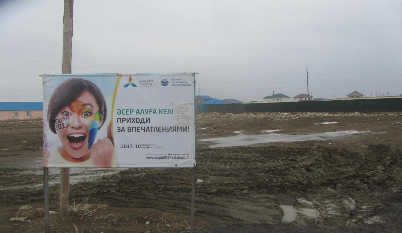 """Утонувший в грязи плакат """"ЭКСПО"""" стоит вблизи трёх сёл Атырауской области"""