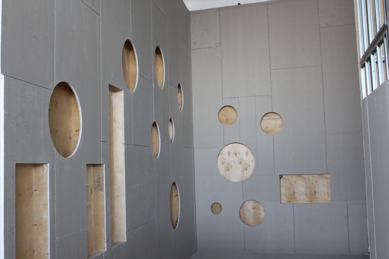 Вырезанные заготовки в виде геометрических фигур на стене павильона