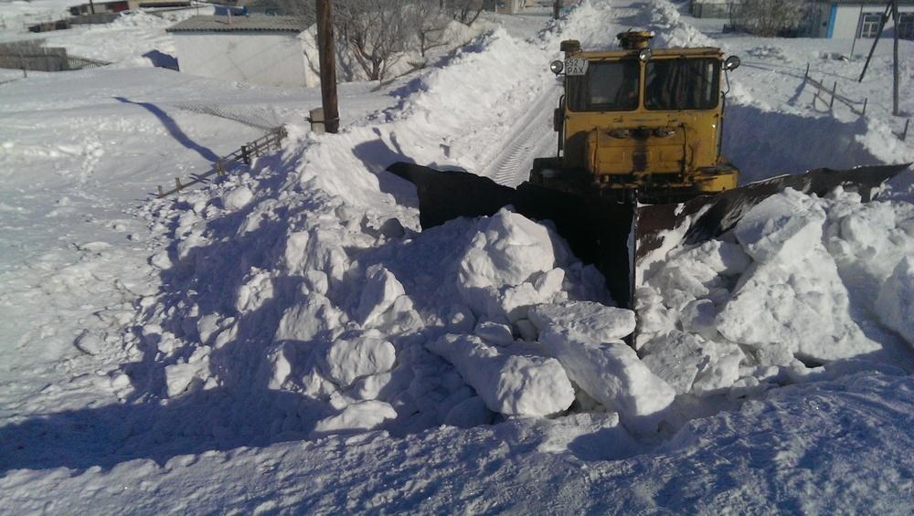 Улицу в селе начала расчищать техника, но снег никуда не вывозят, а сгребают в огромные горы