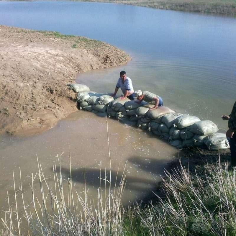 Сельчане помогают перекрывать течение реки на мелководье