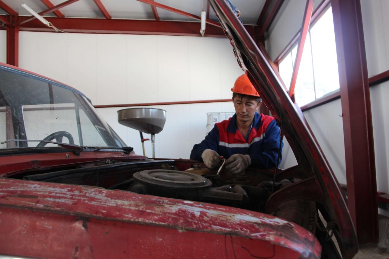 Работник завода занят опустошением автохлама от всех типов жидкости