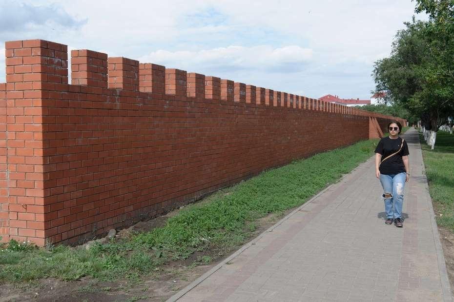 Стена из красного кирпича вдоль мусульманского кладбища