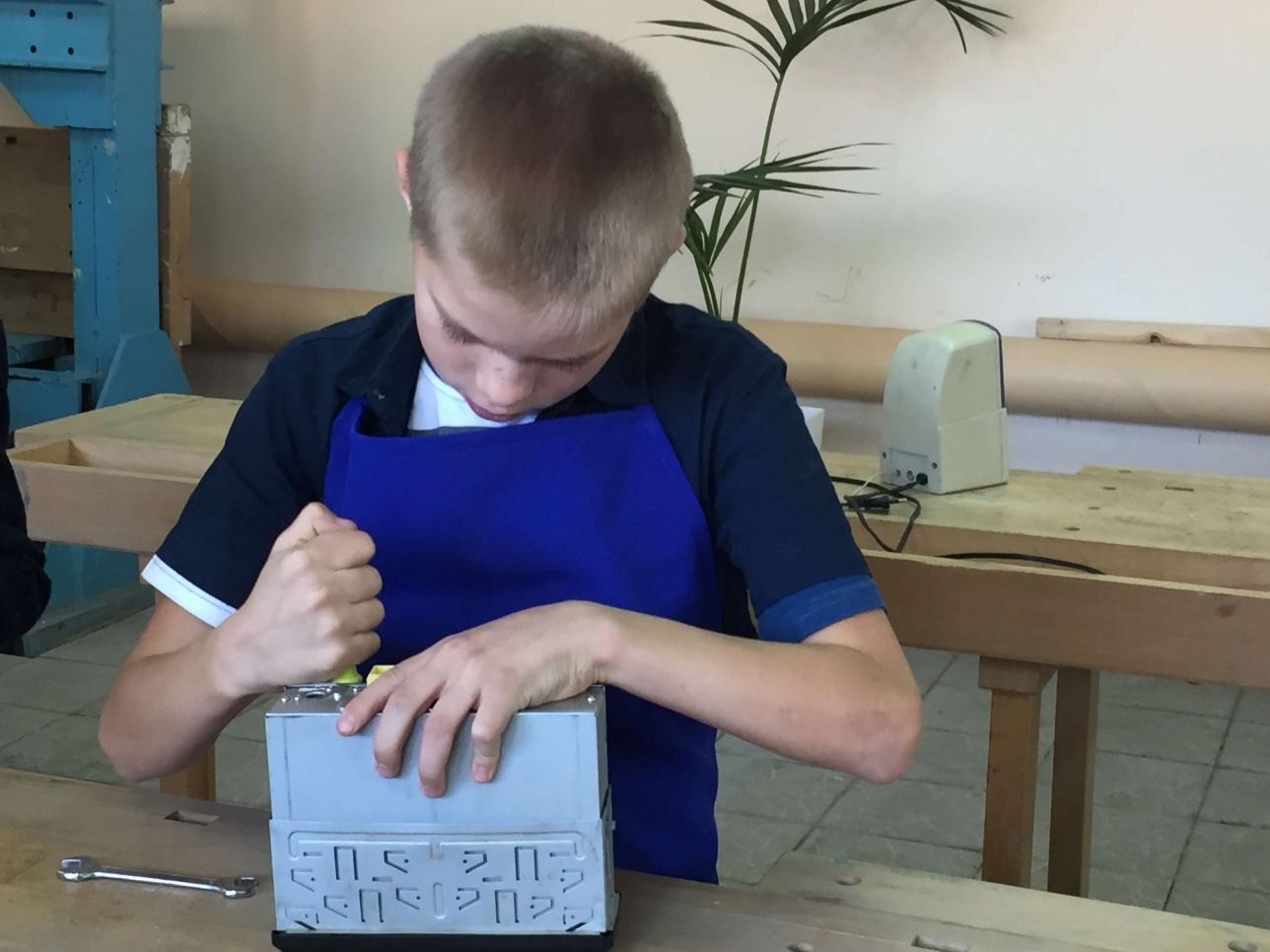 Воспитанник детского дома ремонтирует автомобильную магнитолу.