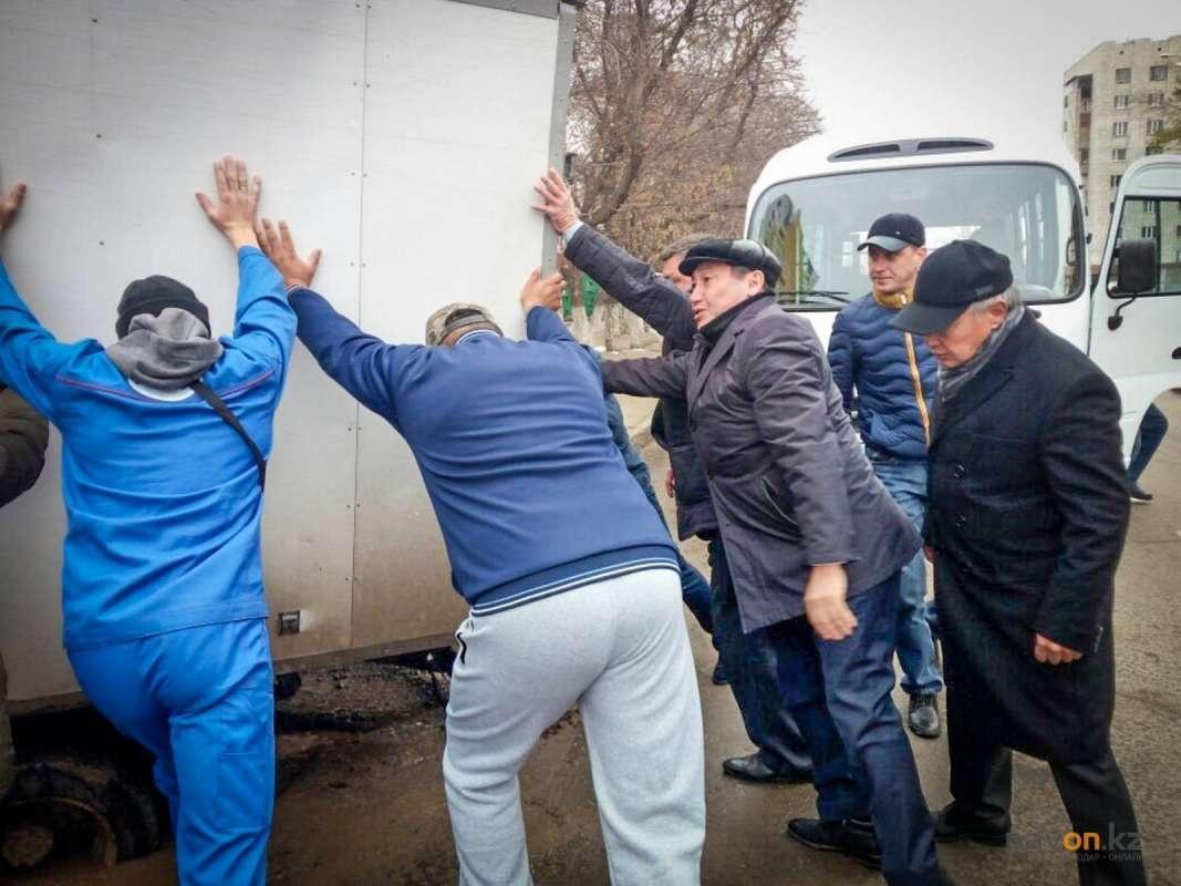 Нуржан Ашимбетов (в кепке) толкает машину