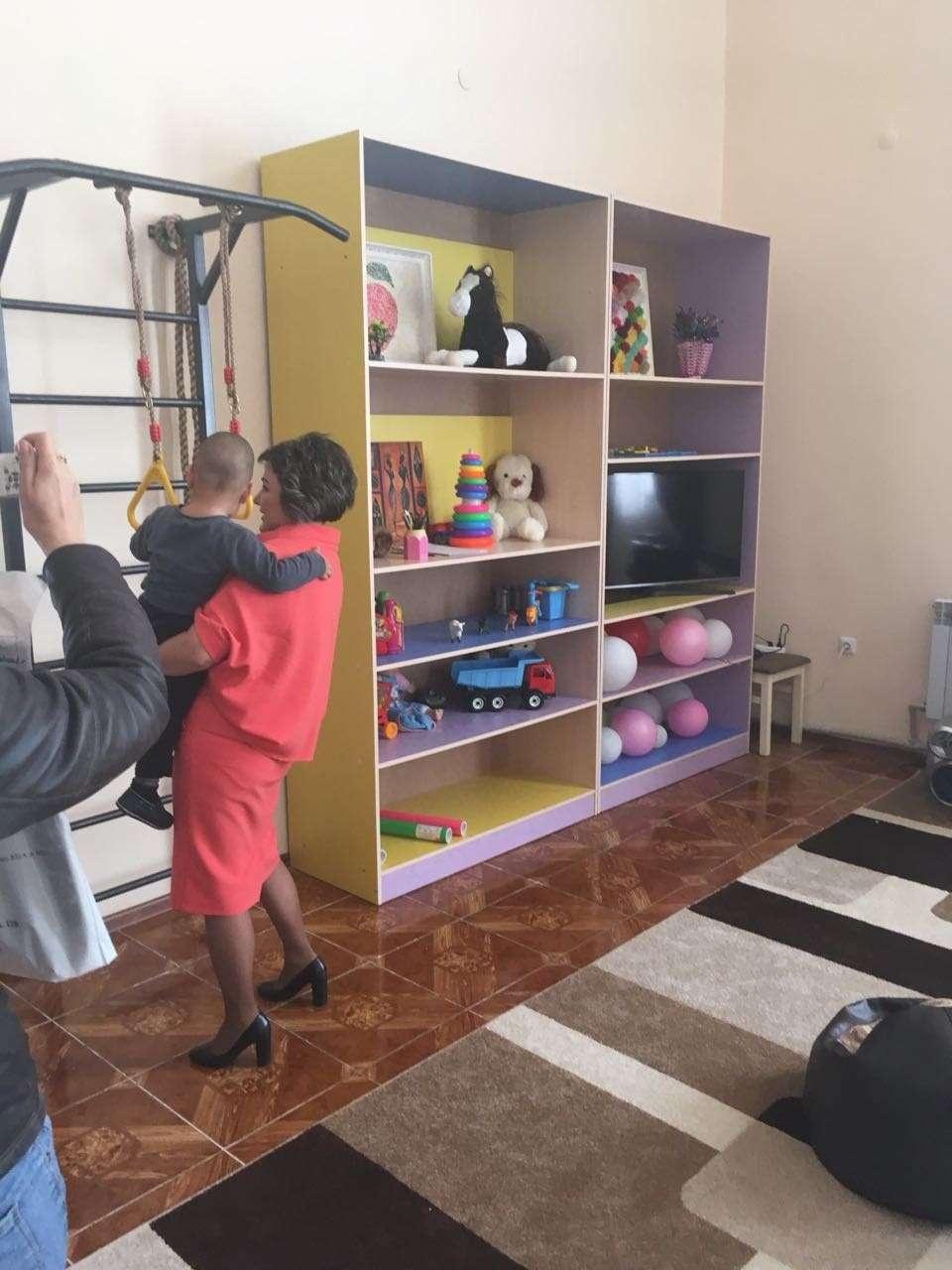Директор приюта играет с ребёнком одной из обратившихся за помощью женщин