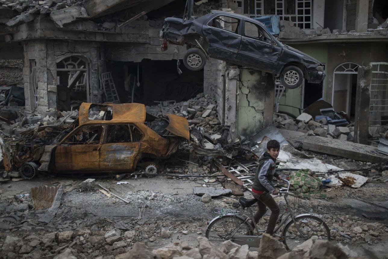 Мальчик едет на велосипеде мимо разрушенных автомобилей и домов в районе, освобождённом иракскими силами, Мосул