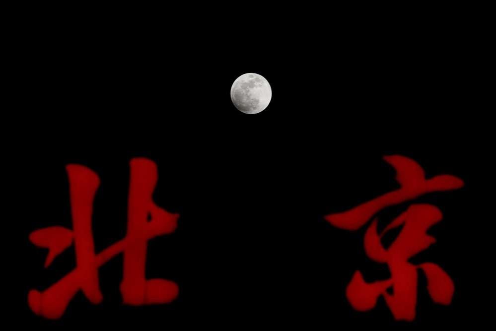 """Луна над надписью """"Пекин"""" на вершине здания в Пекине, Китай"""