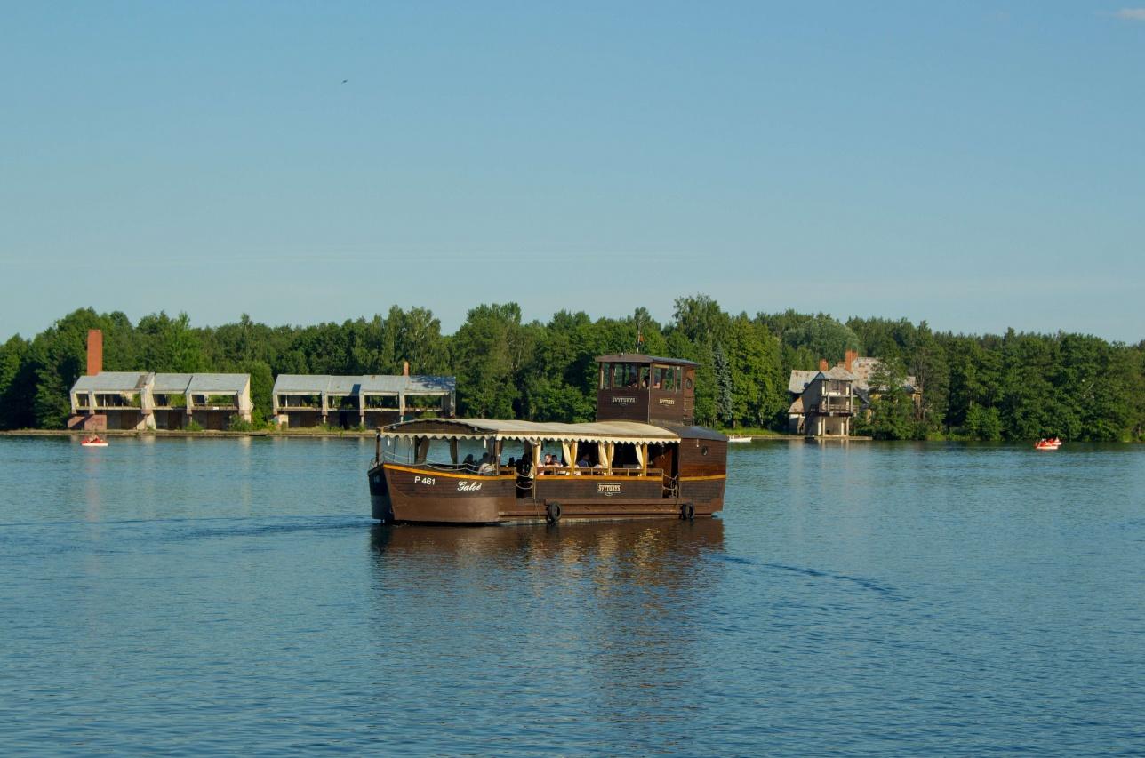 Возле замка по водоёму туристов катает деревянный кораблик