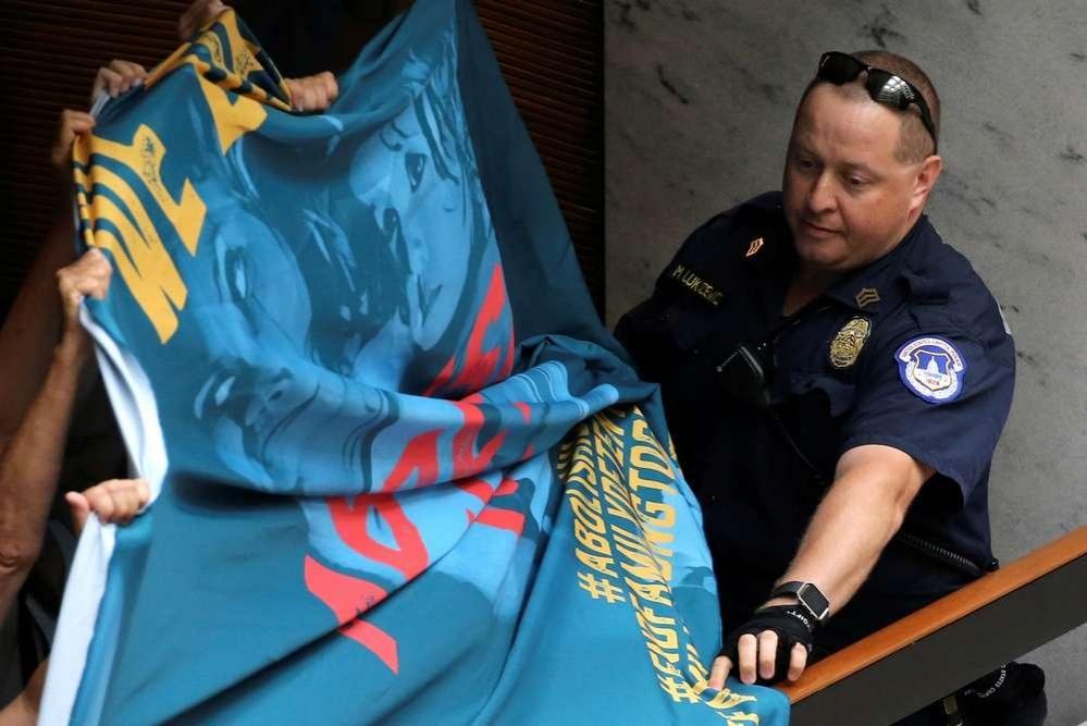 Полицейский отбирает баннер у митингующих