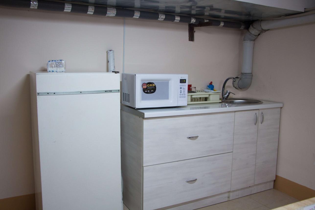 Зона для принятия пищи оснащена холодильником, микроволновой печью, несколькими шкафами, столом
