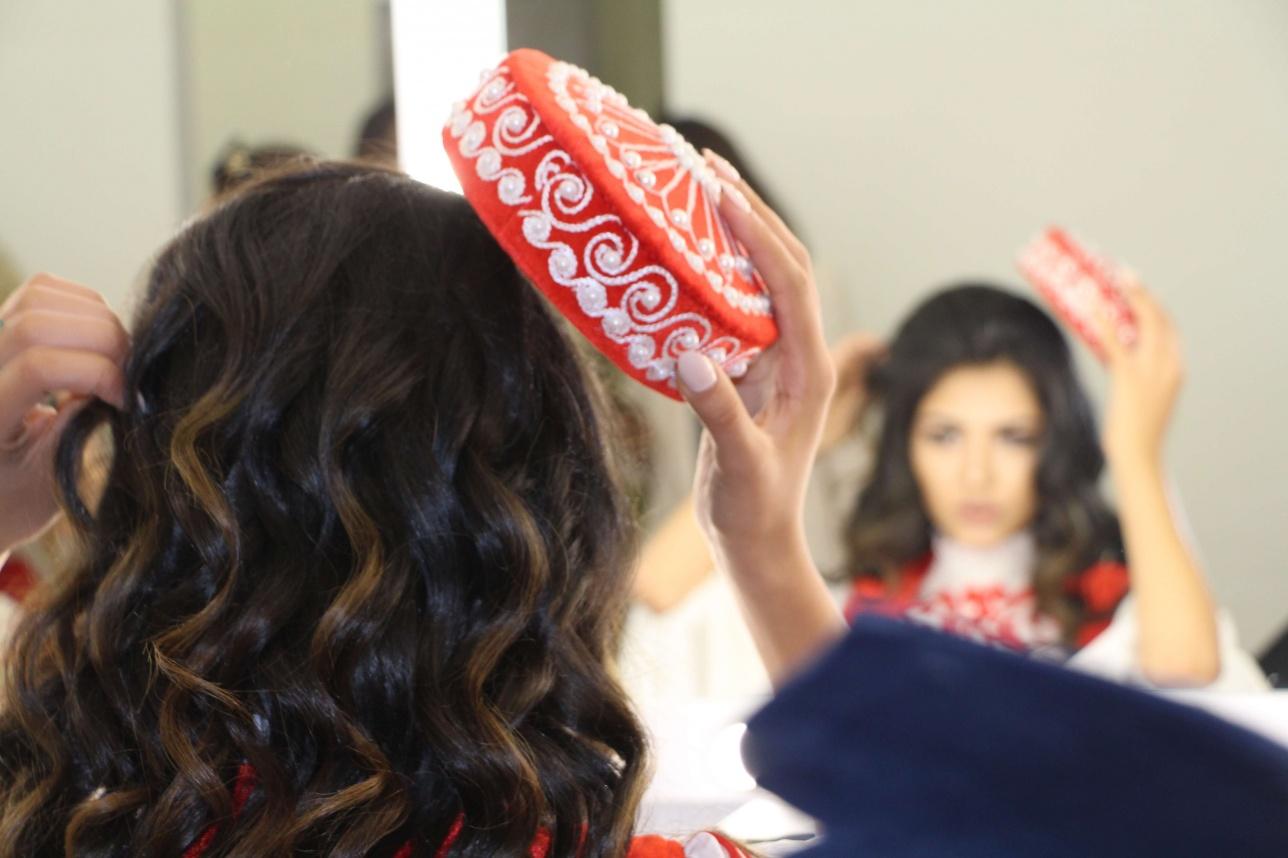 Участница примерят головной убор национального костюма