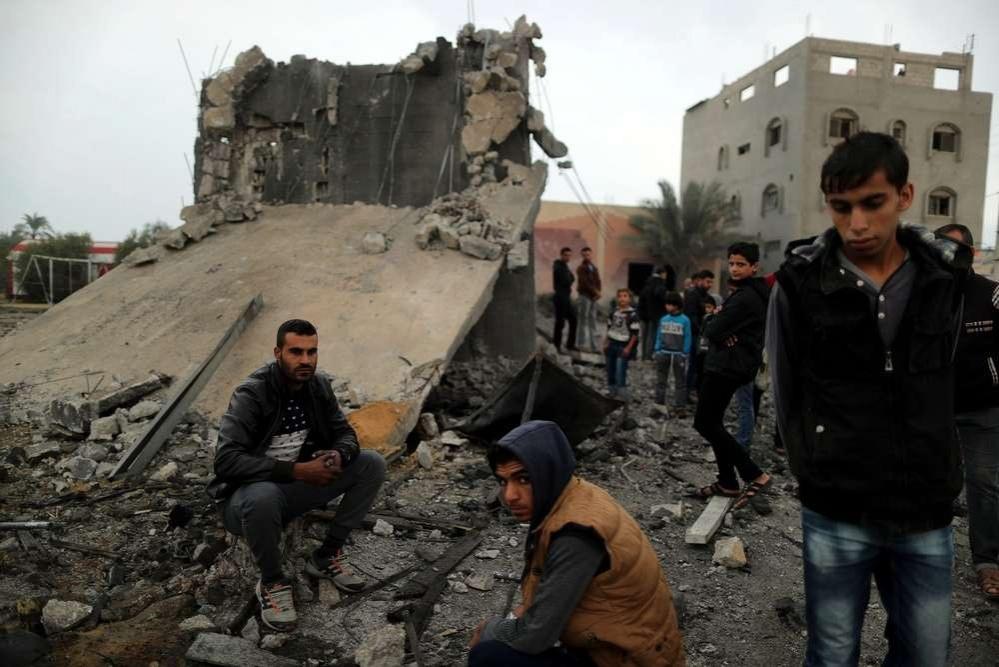 Палестинцы у разрушенного здания после налёта ВВС Израиля