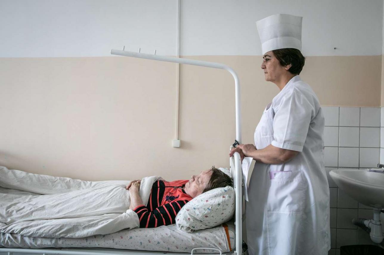 Медсестра хосписа Инерам Имрамзиева у койки пациента