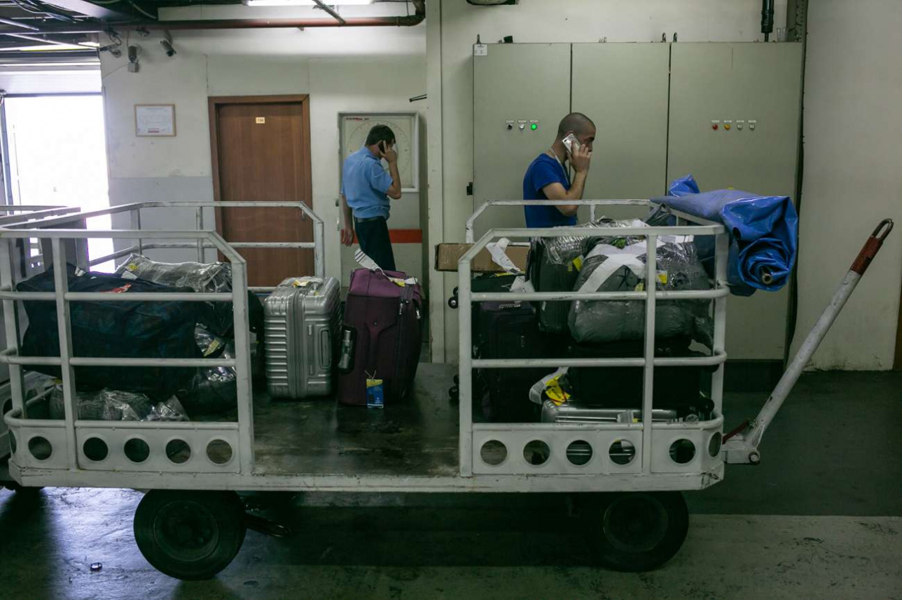 Багаж вручную складывают в тележки