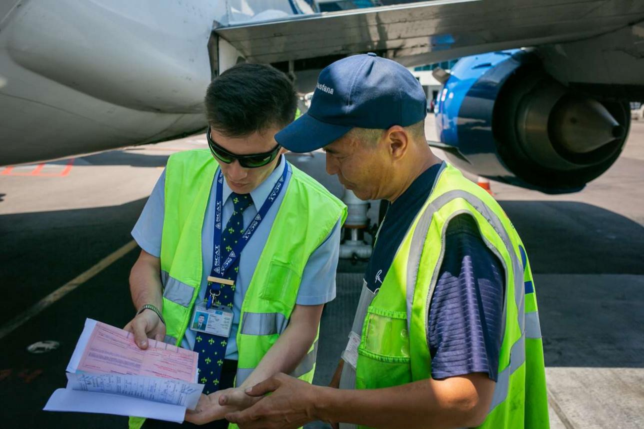 Представитель авиакомпании и приёмосдатчик при выгрузке багажа