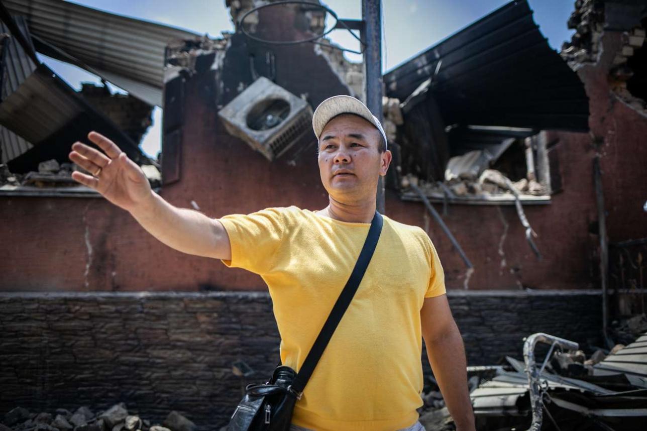 Меиржан Мынбаев на фоне сгоревшего жилого дома брата
