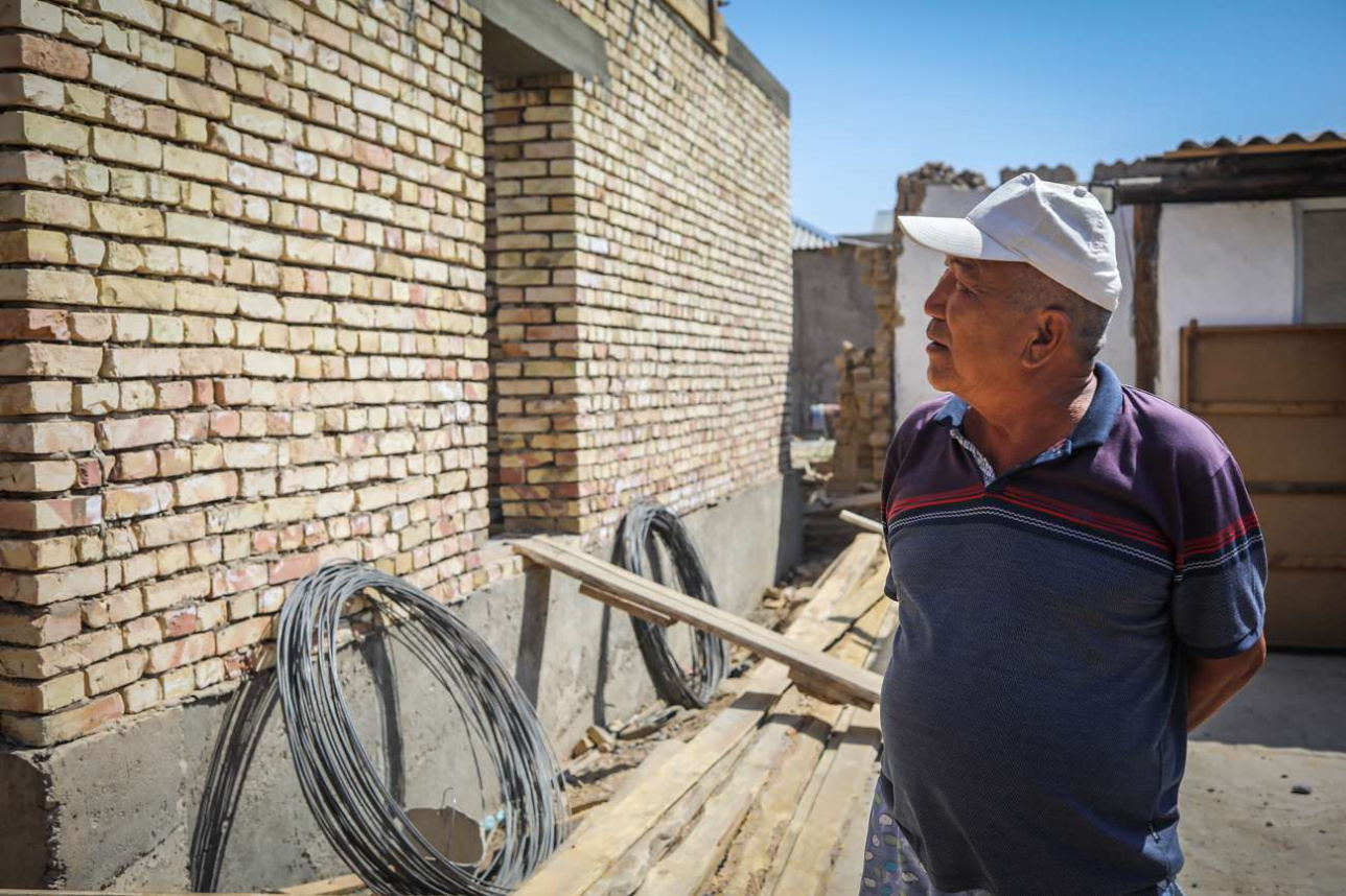 Мамыржан Момынов стоит у строящегося продуктового магазина