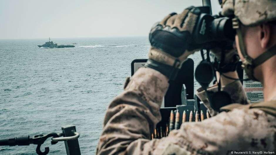 Американский военный наблюдает за иранским военным кораблем в Оманском заливе