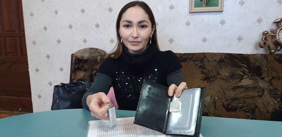 Сноха пенсионера Айнур Карымсакова показывает брелок и портмоне