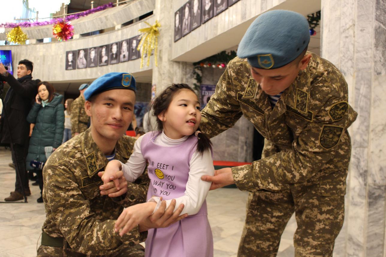 Солдаты помогают детям подниматься и спускаться с лестницы